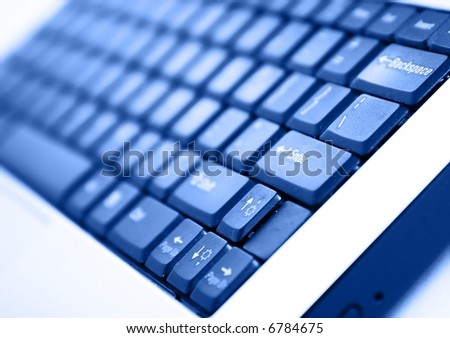 Modern laptop keyboard photographed at a dynamic angle. Selective focus, blue tint