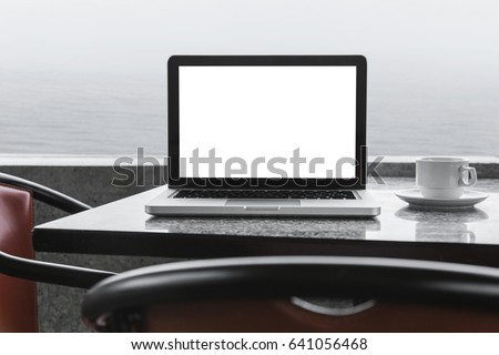 Modern laptop mock up with blank screen on the coffee shop. Sea on the background.