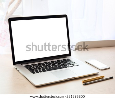 Modern laptop on a table with blank screen - stock photo