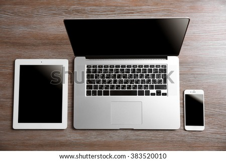 Modern laptop, smart phone and tablet on a wooden table - stock photo