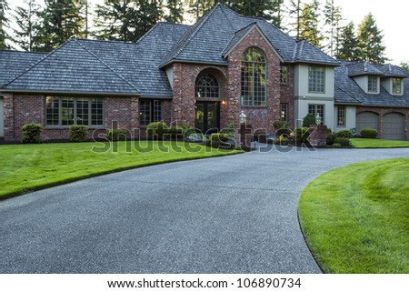 Modern large home with plush green grass in front yard and woods in background - stock photo