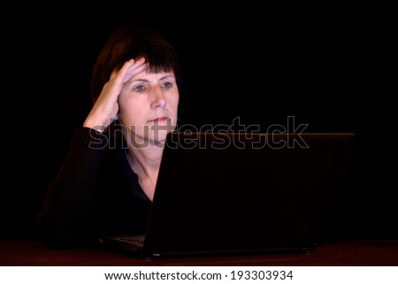 Modern life, working long hours into the night. Woman with laptop, lit by screen. - stock photo