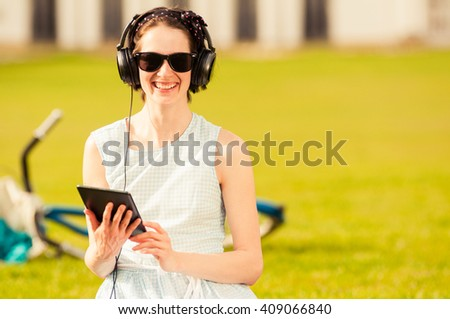 Modern lifestyle and relaxation concept with cheerful woman and tablet smiling and listening to music in the park - stock photo