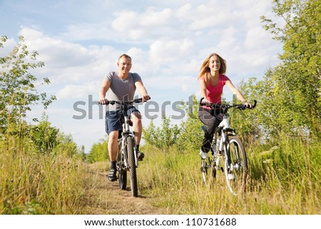 Modern lifestyle : sporty couple riding bicycles