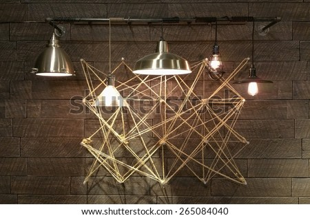 Modern light fixtures hanging in front of complex geometrical design. Abstract Interior design modern and minimal. Light bulbs displaying brightly. - stock photo