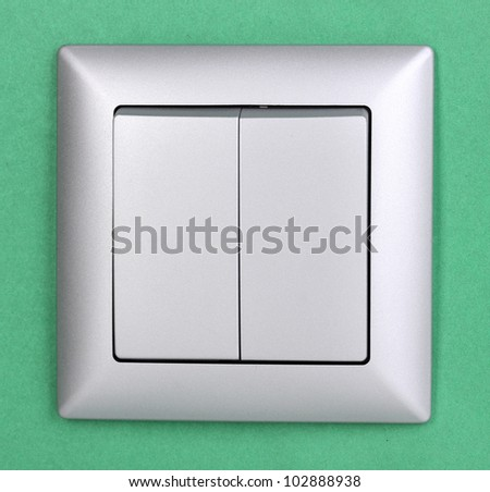 Modern light switch on green background - stock photo