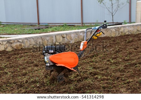 Modern lightweight tiller on the cultivated soil in the autumn garden