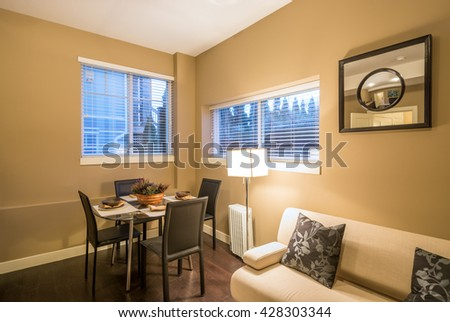 Modern living and dining room interior design with sofa and table set for dinner. - stock photo