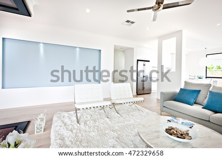 Modern living room and sofa beside a kitchen including a fan on the ceiling under the wool carpet  and sofa with pillows