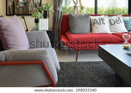 modern living room design with pillows on the red sofa and decorative lamp - stock photo