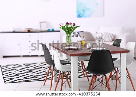 Modern living room. Furniture set with table and chairs. Bouquet of beautiful purple tulips on the table - stock photo