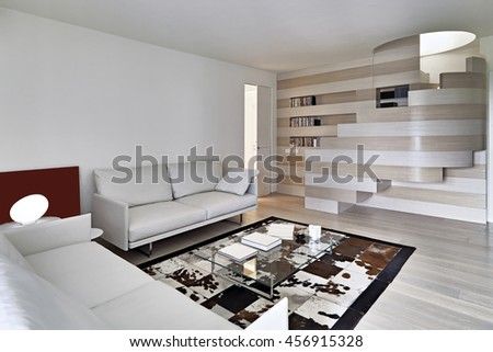 modern living room in foreground the leather sofa overlooking on the big bookcase - stock photo