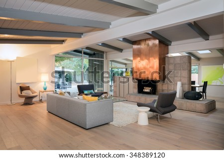 Modern living room interior in mid century home with couch, brass designer fire place, hand-woven natural fine sisal rug, glass table, designer chairs in open space. - stock photo