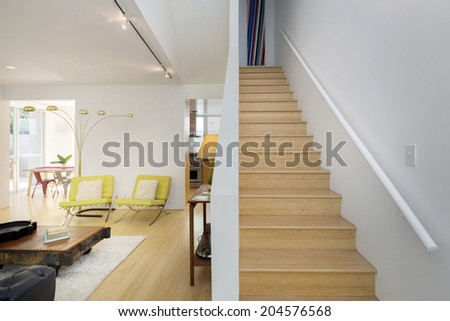 Modern living room interior with adjacent stairway in extraordinary designed modern home - stock photo