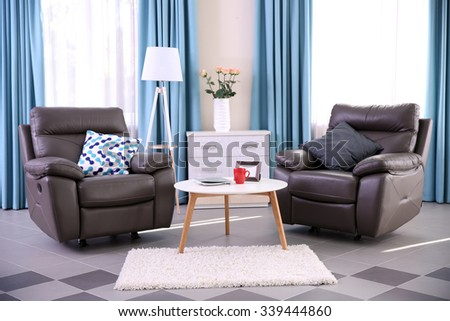 Modern living room interior with coffee table, armchairs and stand - stock photo