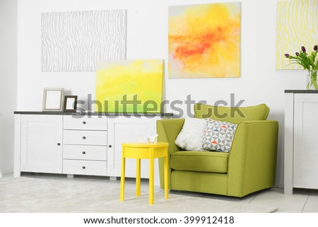 Modern living room interior with green chair, yellow coffee table and bright canvases on the white wall - stock photo