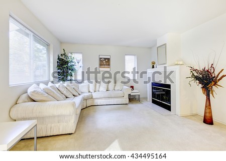 Modern living room interior with white sofa, carpet floor and fireplace. - stock photo