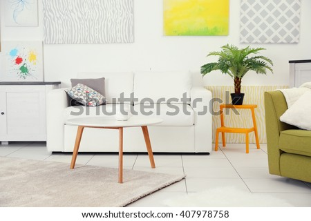 Modern living room interior with white sofa, coffee table and canvases on the white wall - stock photo