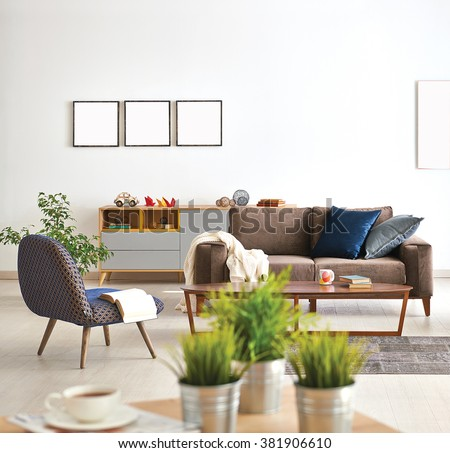 modern living room sofa and armchair with vase of grass - stock photo