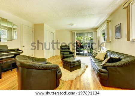 Modern living room with black leather furniture set, piano and ottoman standing on white soft rug. View of walkout deck