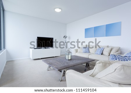 Modern living room with couches and TV in new Australian apartment - stock photo