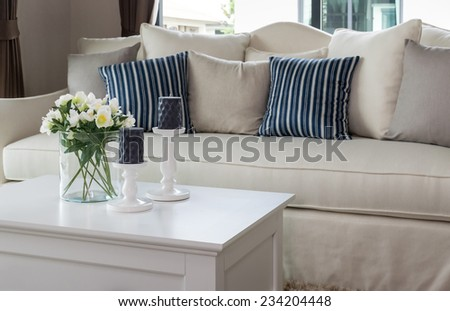 modern living room with glass vase and row of pillows on sofa - stock photo
