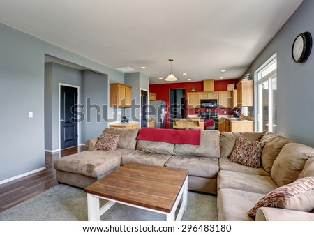 Modern living room with gray walls, including beige sofa and hardwood floor. - stock photo