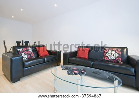 modern living room with leather sofas, cushions and glass coffee table