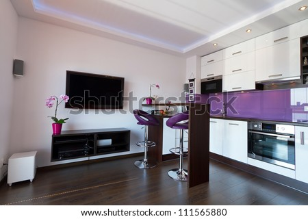 Modern living room with purple kitchen interior