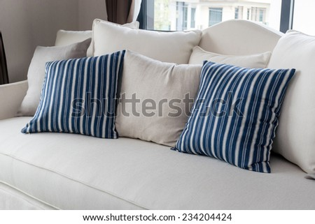 modern living room with row of pillows on sofa at home - stock photo