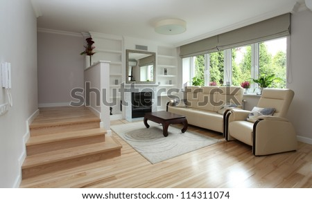 Modern living room with staircase and fireplace - stock photo