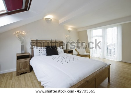 modern loft bedroom with roof windows and balcony access - stock photo