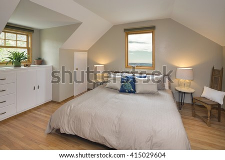 Modern Loft Bedroom with roof windows. Bedroom with build-in furniture under the roof white sheets, night stands and wooden floor. - stock photo