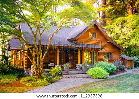Modern Log Cabin Home in a Forest Environment - stock photo