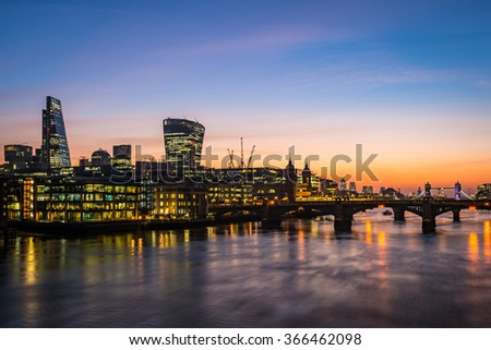 Modern London, morning photo with offices by the river Thames and illuminated towers - stock photo