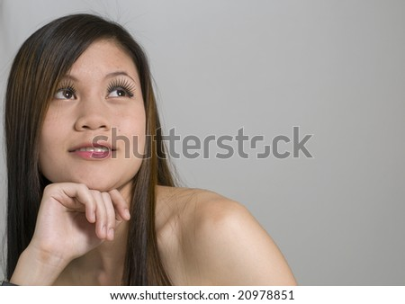 Modern looking Asian woman resting her head on her hand and looking away - stock photo