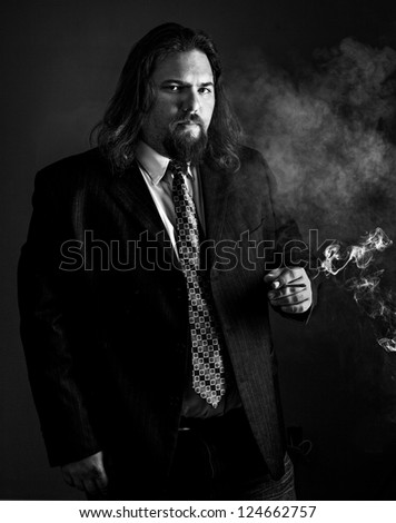 modern looking white man with long hair wearing a sport coat and tie smoking a cigarette.
