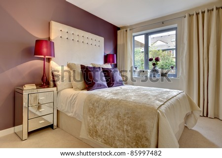 Modern luxury bedroom stylishly dressed with fashionable brightly coloured fabrics
