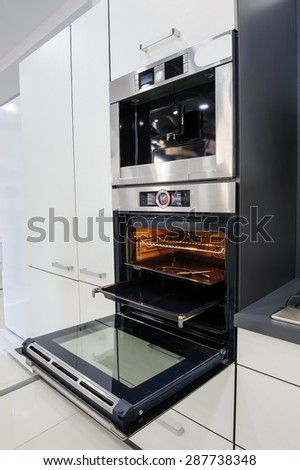 Modern luxury black and white kitchen, clean interior design, focus at oven with door open - stock photo