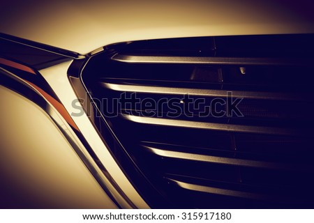Modern luxury car close-up of grille. Gold background, concept of expensive, sports auto detailing - stock photo