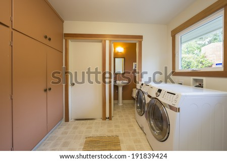Modern luxury in chestnut brown laundry room with adjacent bathroom and washer and dryer with tile floor. - stock photo