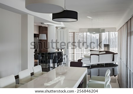 Modern luxury interior in minimalistic style: living room with big table and kitchen in daylight