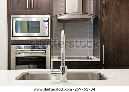 Modern luxury kitchen interior with stone countertop and stainless steel appliances - stock photo