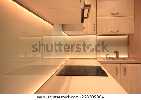 Modern luxury kitchen with yellow LED lighting - stock photo