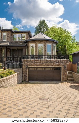 Modern luxury residential house with tile paved driveway on cloudy sky background. High end family home with rotunda above double garage - stock photo