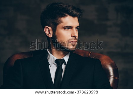 Modern man.Portrait of young handsome man in suit holding his sunglasses and looking at camera while sitting in leather chair against dark grey background