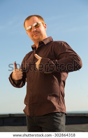 Modern man showing OK sign with his thumb up. Young man in sunglasses against the blue sky. Selective focus on face. Young handsome man with thumbs up. Male model showing success. - stock photo