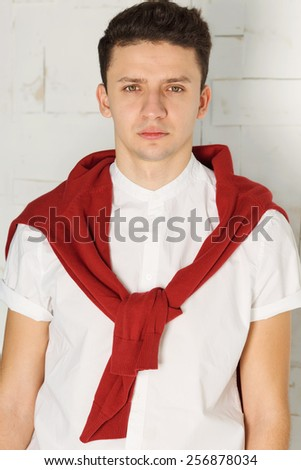Modern man wearing white shirt and red jacket on the shoulders on white background.  Elegant young handsome man. Studio fashion portrait. Portrait of a smart young man in white shirt with arms crossed - stock photo