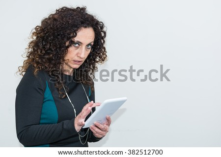Modern mature woman, angry, use the tablet. She has long curly hair and blacks, with green eyes. Enraged, he gets angry with his work tool. - stock photo