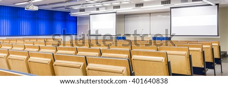 Modern medical university with spacious lecture hall with two screens - stock photo